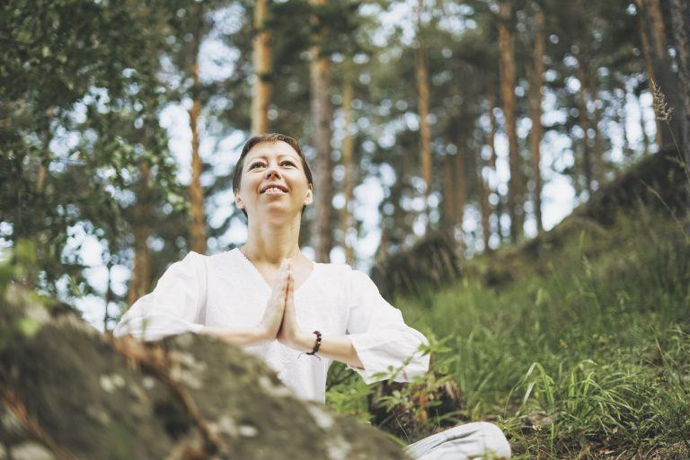 Young smiling woman practice yoga outdoors in forest